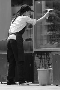 Frau bei einer Fensterreinigung
